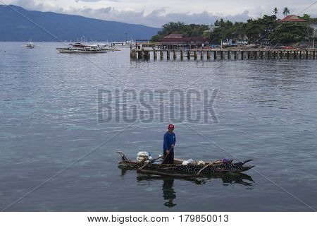7 March 2017 - Cebu Philippines: fisherman in traditional wooden boat near pier. Filippino fisherman in sea. Whale shark design boat. Pinoy people daily lifestyle. Tropical seashore rain season