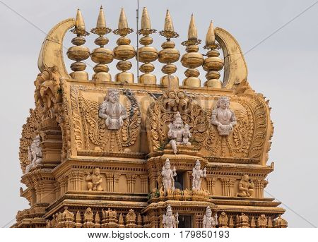 Nanjangud India - October 26 2013: Focus on the elaborately decorated Kalasam of the main Gopuram of Sri Srikanteshware temple in Ganjangud Karnataka State. Golden decoration white statues.