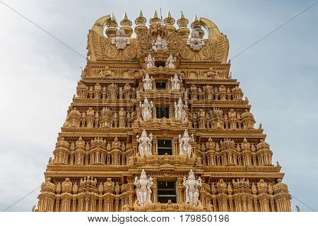 Nanjangud India - October 26 2013: The elaborately decorated Kalasam and top five levels of the main Gopuram of Sri Srikanteshware temple in Ganjangud Karnataka State. Golden decoration white statues.
