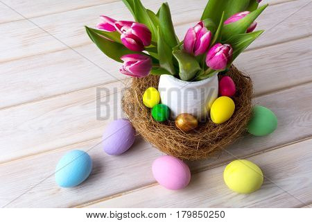 Easter table centerpiece with pastel color hand painted eggs in nest and pink tulips. Happy Easter greeting card.Copy space.