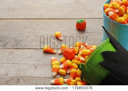 Buckets with tasty Halloween candies on wooden background