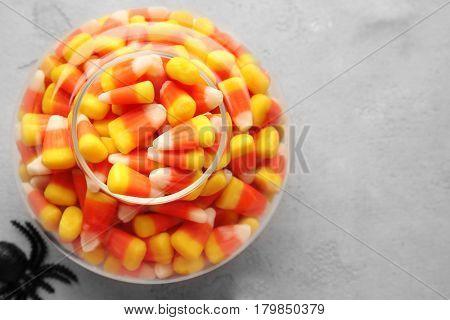 Vase with tasty Halloween candies on light background