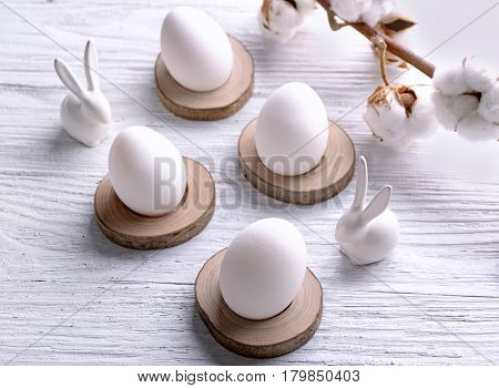 Easter eggs, branch of cotton and rabbits on white background