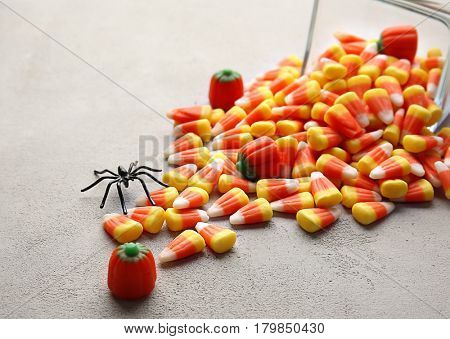 Glass bowl and tasty Halloween candies on light background