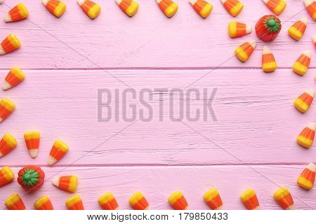 Frame made of tasty Halloween candies on wooden background