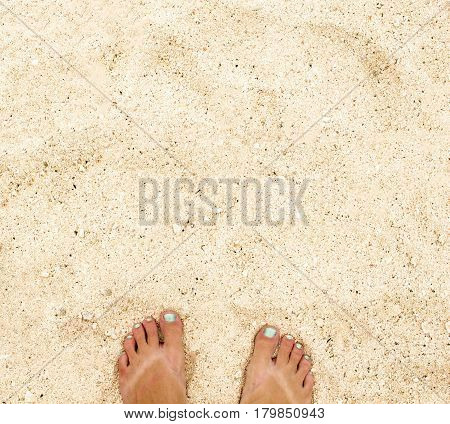 Woman's feet on warm white sand. Yellow sand beach top view photo. Seaside vacation banner template with text place. Holiday travel to seashore. Mermaid pedicure on girl's feet. Summer weekend by sea