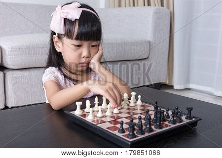 Aerial View Of Asian Chinese Little Girl Concentrating On Chess