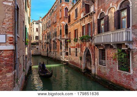 Gondola on narrow canal among old brick houses in Venice, Italy.