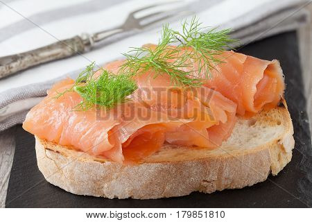 Smoked salmon with fresh dill on bread slice in natural light authentic food.