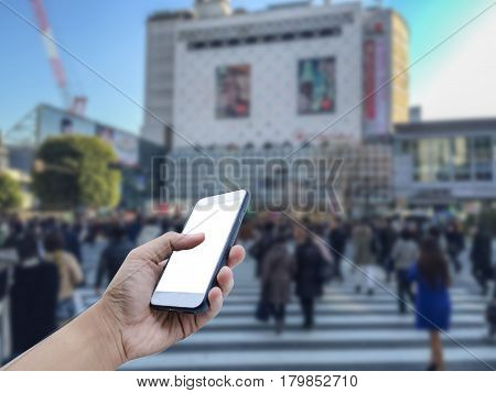 Hand holding mobile smart phone with a crowd of people in Shibuya Crossing