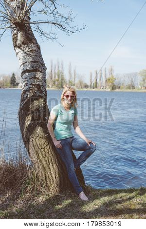 Young woman resting in summer park. One tree and lake on background.