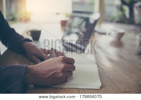 Close shot of a business man hand writing something on notebook on the foreground with vintage filter
