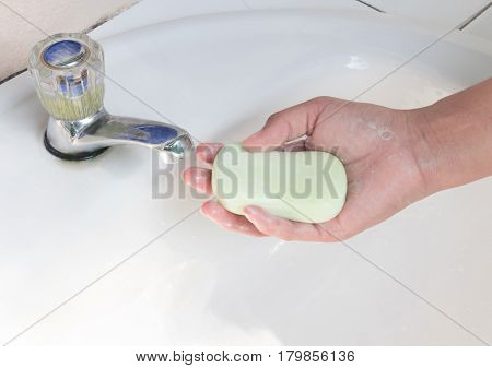Woman hand holding soap for washing hand with light of sun form park health care concept