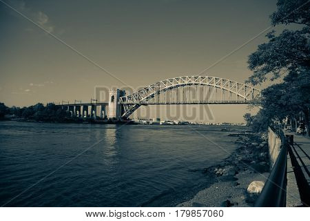 The Hell Gate Bridge and the shore in vintage style at Astoria Park, New York