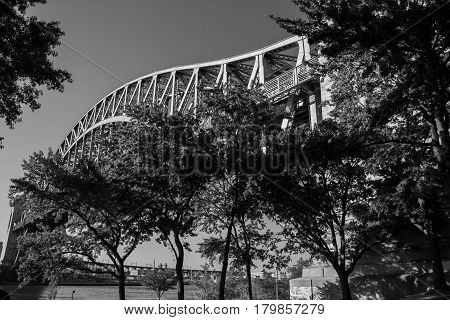 Hell Gate Bridge over the river and trees at Astoria park in black and white style, New York
