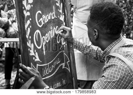 Adult Man Writing Grand Opening Sign