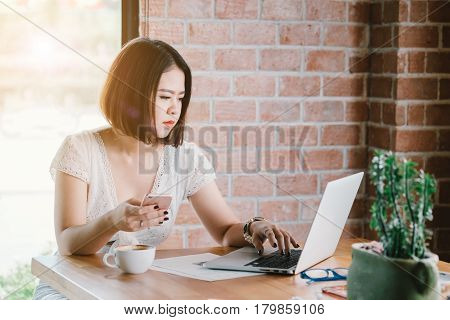 A beautiful asia woman is smiling while is using a smart-phone and a laptop computer in coffee cafe shop