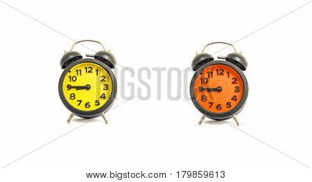 Closeup yellow alarm clock and orange alarm clock for decorate show a quarter to nine a.m. or 8:45 a.m. isolated on white background
