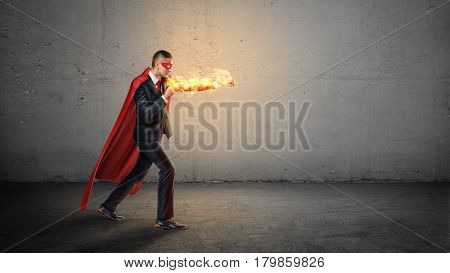 A businessman in a red superhero cape and a flaming hand throwing punches at an invisible enemy on concrete background. Superpowers. Overcoming difficulties. Fight for success.