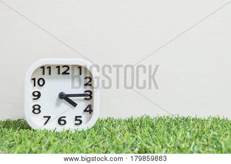Closeup white clock for decorate show a quarter past four o'clock or 4:15 p.m. on green artificial grass floor and cream wallpaper textured background with copy space
