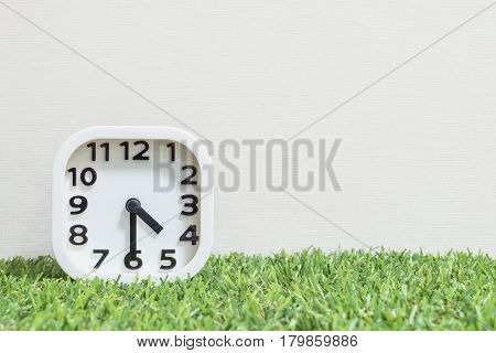Closeup white clock for decorate show a half past four o'clock or 4:30 p.m. on green artificial grass floor and cream wallpaper textured background with copy space
