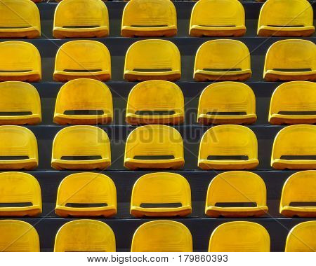 Empty plastic yellow seats on the stadium