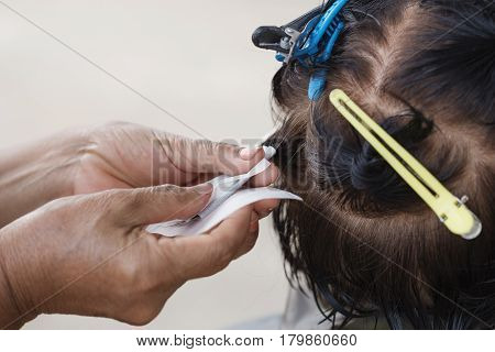 Hand Of A Hairstylist Doing A Perm Rolling Hair Of Senior Woman