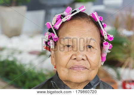 asian senior woman with the hair roller