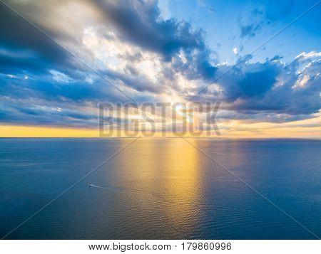 Aerial Panoramic View Of Lonely Boat Sailing Across Ocean At Beautiful Sunset. Beautiful Glowing Yel