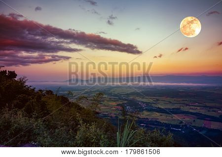 The full moon in the evening after sunset. Scenes from view point with colorful sky. Outdoors at nighttime. Vintage tone.