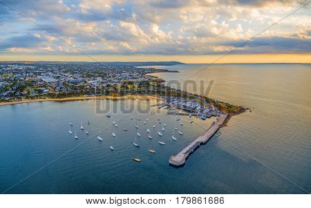 Aerial Panorama Of Mornington Pier And Coastline At Sunset. Moored Boats And Suburban Area Under Bea