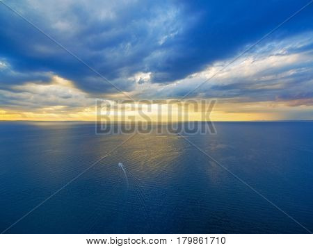 Aerial View Of Lonely Boat Sailing Across Ocean At Beautiful Sunset.