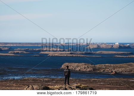 Traveler man standing on rock with serene view of archipelago island