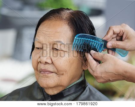 Hand Use Comb To Dressing Hair Of A Senior Woman