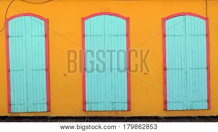 Detail of the facade of a colorful Creole house with sidewalk. Painted wooden door. Natural light and colors. Guadeloupe, French West Indies.