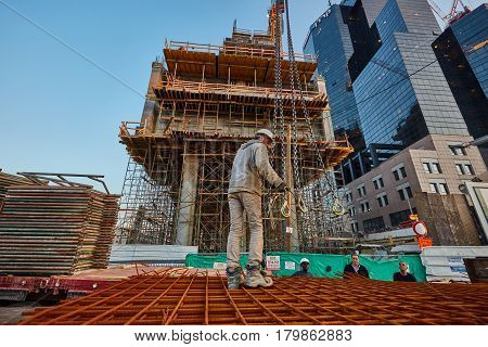 Tel-aviv - 9 December, 2016: A Worker In A Construction Site Connects The Crane Hook To Rusty Fittin
