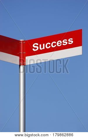 road signpost with success text in front blue sky