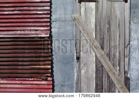 Detail of the facade of an abandoned Creole house. Metal wall, old corrugated iron and wooden door. Naturally patined by time and elements. Photographed in Guadeloupe, French West Indies.