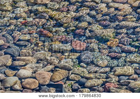 Colorful rocks under moving water in a creek