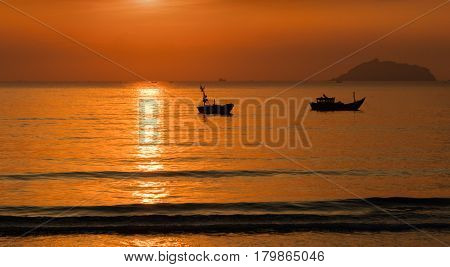 A fiery orange sunrise sky looking out over the south China sea in Vung Lam Bay Vietnam. With fishing boats in silhouette.