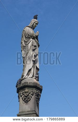 Maria sculpture made of stone with a dove on the head  Mary's column from Kaspar von Zumbusch 1861 in Paderborn blue sky with copy space vertical