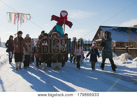 Kazan, Russia - 28 february 2017 - Sviyazhsk Island : The pancake week - Russian ethnic carnival Maslenitsa, Shrovetide the crowd carries the effigy of winter to burn, snow sunny day