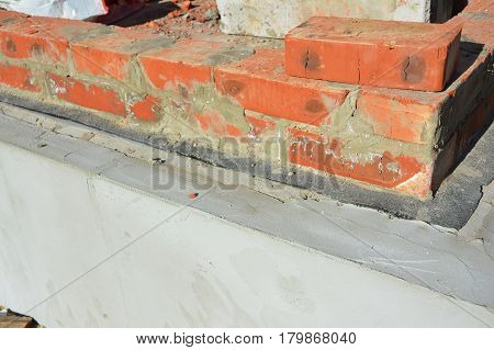 Damp proof membrane on top of foundation walls.