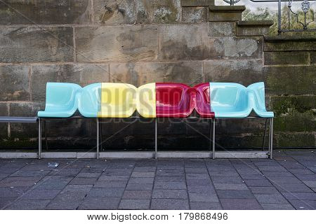 PADERBORN GERMANY MARCH 13 2017: bench with colorful designer chairs from plastic on the road in front of a wall of old dark sand stone