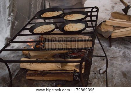 The pancakes are fried in a pan outdors - maslenitsa carnival, close up