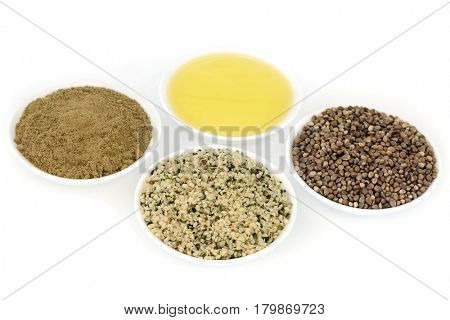 Hemp health food ingredients with powder, hulled seed, oil and dried seeds in porcelain bowls on white background.
