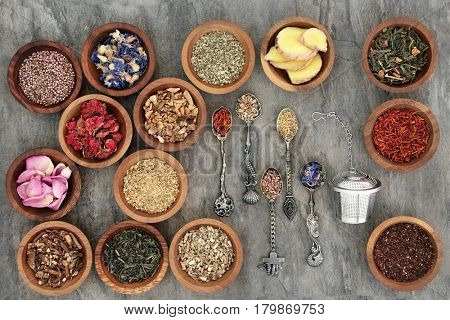 Herb tea varieties in old spoons and wooden bowls with strainer, teas also used in natural alternative medicine.