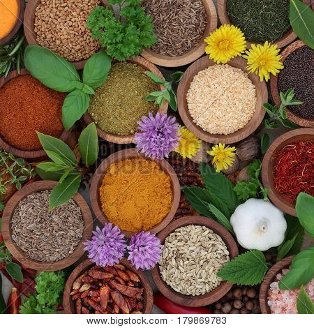 Herb and spice seasoning in wooden bowls and loose forming a background, high in antioxidants and vitamins.