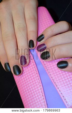 Hands with manicure - black and purple gel polish with a matte topom