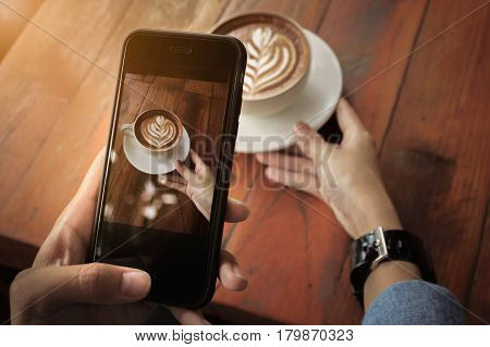 Young girl using Photography of smartphone of latte art coffee on mobile camera display while shooting.